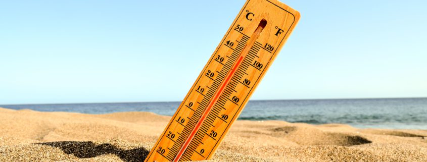 A selective focus shot of a thermometer in the beach sand with a blurred background ( calor, energía, ola de calor, ...)